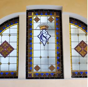 Windows with decorative polychrome glasses and with the monogram of the Sant'Elia family